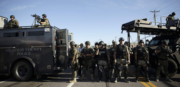 Police in riot gear watch protesters in Ferguson, Mo. on Wednesday, Aug. 13, 2014. (AP Photo/Jeff Roberson)